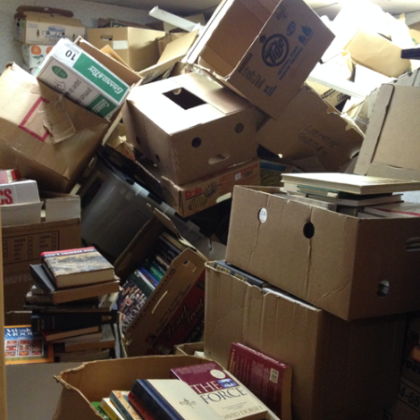 A room filled completely with boxes of books and boxes probably formerly filled with books.
